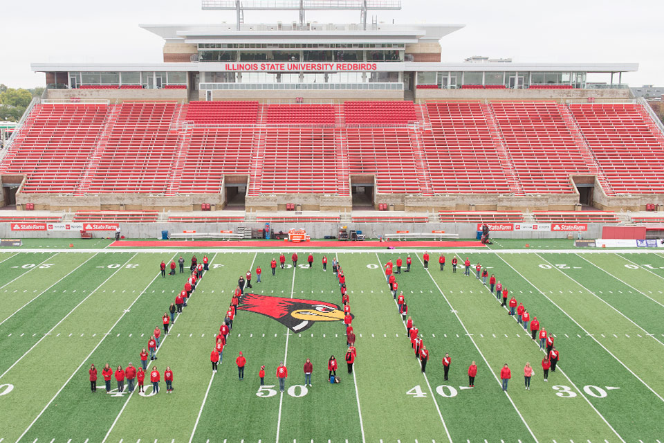 MCN faculty and staff form a number 100 on the football field
